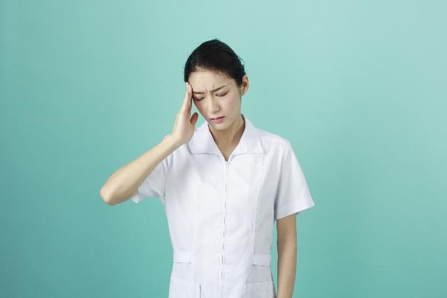 こめかみを抑える看護師